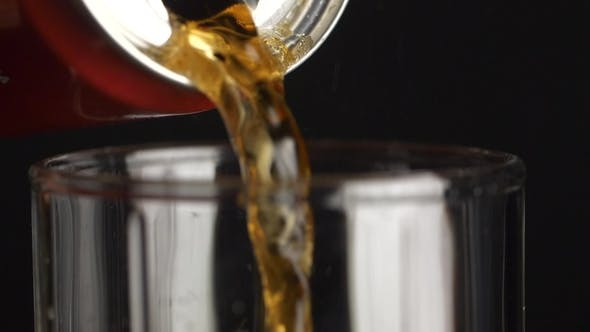 Cover Image for Pouring Glass of Soda Drink. .  Pouring of a Brown Beverage From a Aluminum Bottle