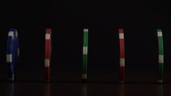 Thumbnail for Poker Chips Stand in a Row on a Black Background, a Domino Effect. Playing Poker Chips Are on the