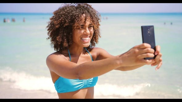 Thumbnail for Cheerful Ethnic Woman Taking Selfie on Beach