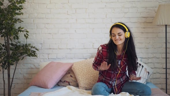 Thumbnail for the Girl Listens To Music with Headphones and Sitting on the Bed Dancing