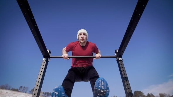 Thumbnail for Young Strong Athlet Doing Pull Ups on a Bar on the Nature in Winter.