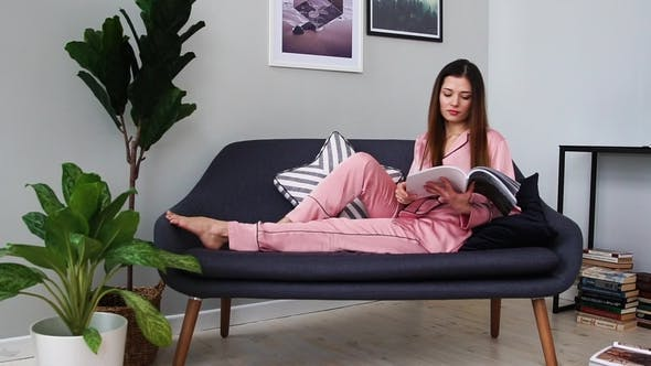 Thumbnail for Beautiful Girl in Sexy Pink Pajamas Reads a Magazine Lying on the Couch and Drinking
