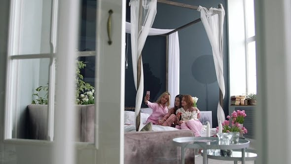 Thumbnail for Three Sexy Girls in Pajamas Sitting on the Bed Drinking Champagne and Taking Selfies