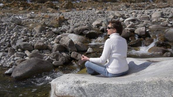 Cover Image for Frau mittleren Alters sitzt in einem Lotus Pose in der Nähe eines Gebirgsflusses