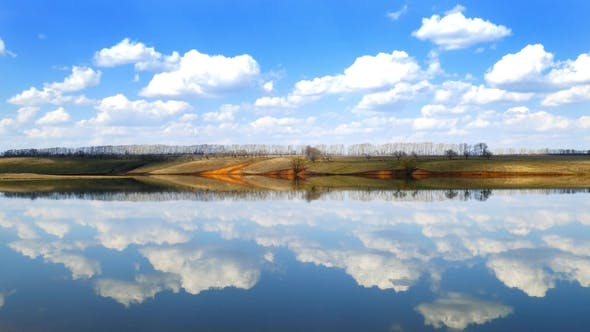 Thumbnail for Clouds Are Reflected in Smooth Water of Lake,