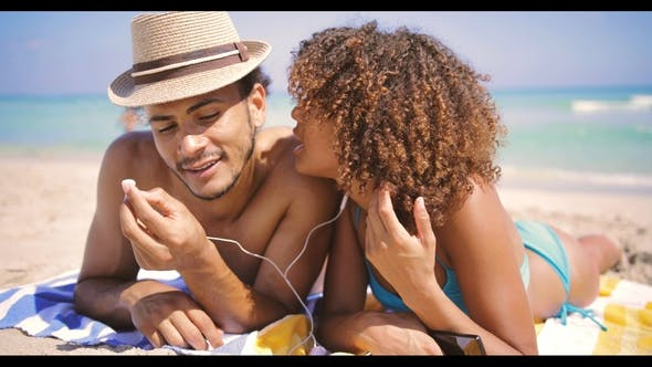 Thumbnail for Couple Lying with Music on Beach