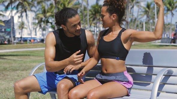 Woman Showing Bicep To Boyfriend