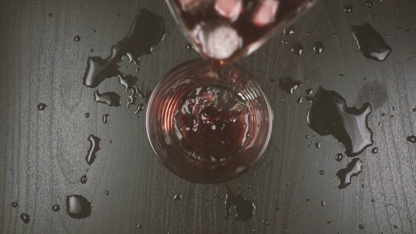 Thumbnail for Red Wine Diluted with Water and Ice Is Poured Into a Glass
