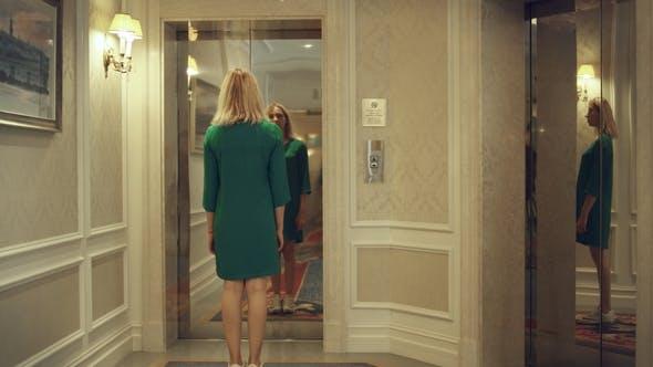 Thumbnail for Junge Frau Druckknopf zum Anrufen von Aufzug und Warten in der Wohnung