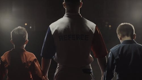 Boys Athletes and Referee Who Raises the Hand of the Winner. The Referee Raises the
