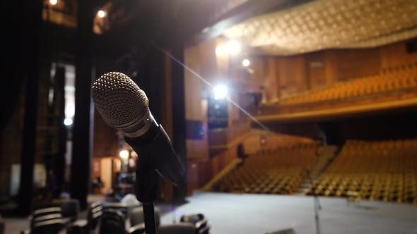 Microphone on the Stage and Empty Hall During the Rehearsal. Microphone on Stage with Stage-lights