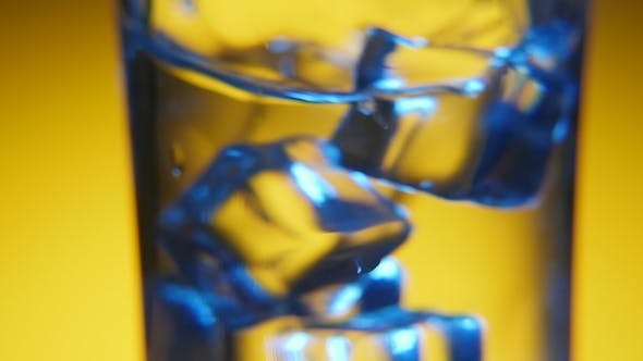 Thumbnail for Five Ice Cubes Are Shaken in a Crystal-clear Glass in the Yellow Background