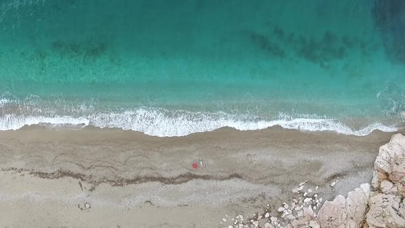 Thumbnail for Young Woman Lying on the Back Near the Waves of Blue Sea. Footage. Top View