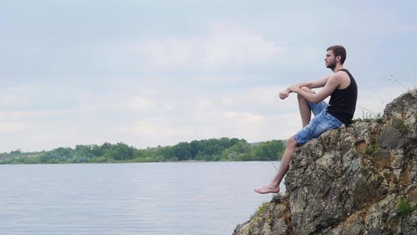 Thumbnail for Young Man Sitting on a Rock Cliff Above a Rural Lake. Country Boy. Lonely Young Man