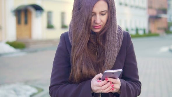 Thumbnail for Young Woman Uses a Mobile Phone in the City