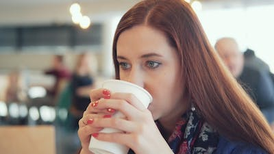 Woman Is Drinking a Drink in a Cafe