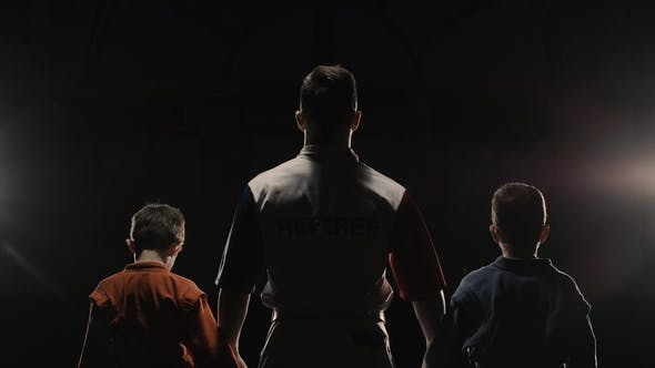 Thumbnail for Rear View of the Boys Athletes and Referee Who Raises the Hand of the Winner. The Referee Raises the