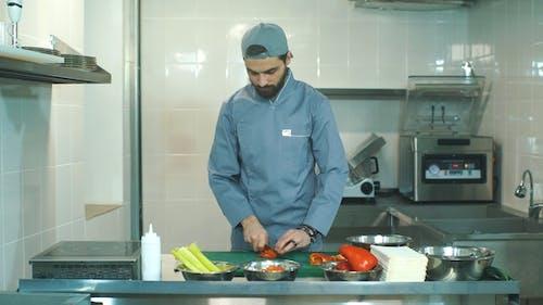The Chef in Blue Apron Cuts Pepper