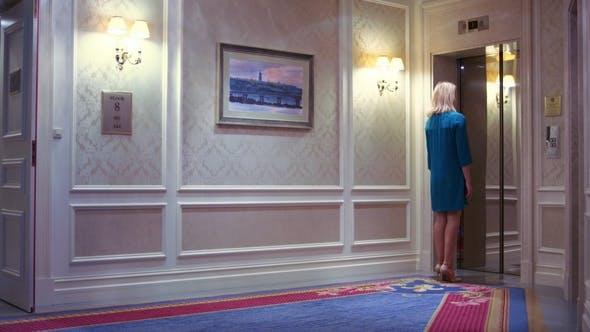 Junge Frau kommt zu heben Türen und drücken Taste für Anrufe im Hotel