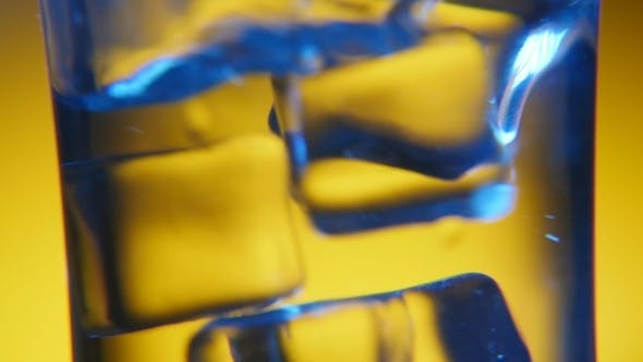 Thumbnail for Five Ice Cubes Are Dancing in a Clear Glass in the Golden Background