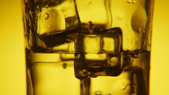 Thumbnail for Golden Ice Cubes in a Glass and Water Pouring in It with Shining Bubbles