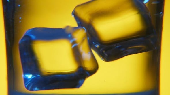 Thumbnail for Several Cubes of Ice Are Thrown Into a Glass with Transparent Water in Studio