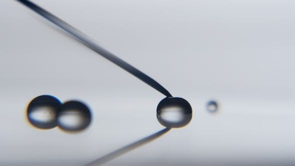 Cover Image for Crystaline Water Drop Gets Big Touching a Metallic Needle in a Scientific Lab