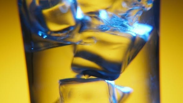 Thumbnail for Several Ice Cubes Are Dancing in a Clear Glass in the Yellow Background