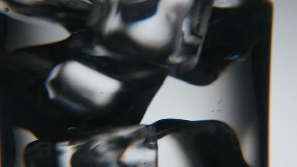 Cover Image for Black and White Ice Cubes Are Shaken in a Clear Glass in the Grey Background