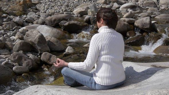 Thumbnail for frau meditieren neben ein berg strom