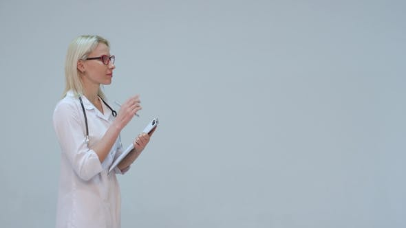 Thumbnail for Woman Doctor Writing on a Clipboard While Smiling Against a Grey Background