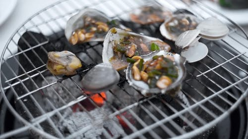 Mussels Are Roasted in the Sauce on the Open Fire of Grill, Cooking of Shellfish Outdoors, Seafood
