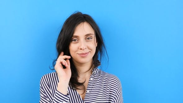 Cover Image for Happy Woman Plays with Her Hair and Smiles on Blue Background