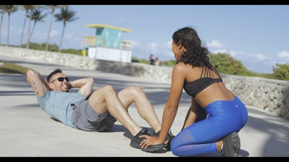 Thumbnail for Girl Helping Man with Abs Exercise