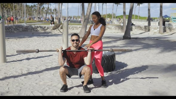 Thumbnail for Woman Helping Man with Workout on Beach