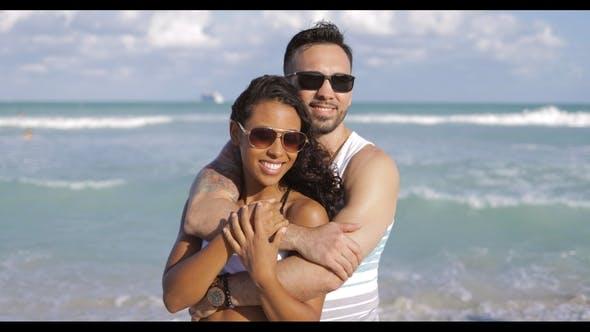 Embracing Diverse Couple on Shoreline