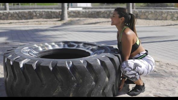 Frau versucht, den Reifen zu heben