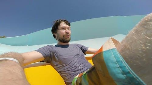 Young Man Sliding Down at the Aquapark