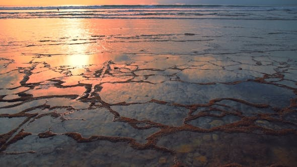 Cover Image for Beach at Low Tide with the Reflection of the Sky in the Water During Sunset