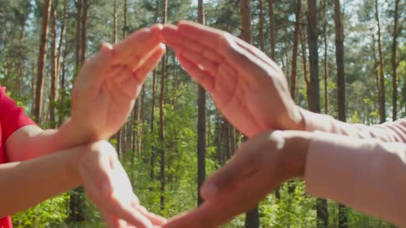 Couple Showing Shape of Earth with Hands Outdoors