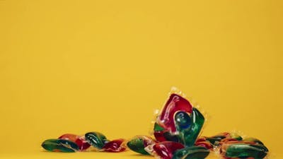 Throwing Washing Gel Pods on Yellow Background Capsules with Detergent for Washing Machines