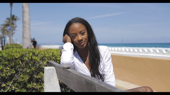 Thumbnail for Attraktive junge Frau sitzt auf Bank am Meer