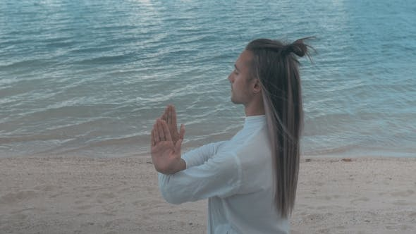 Thumbnail for Man Doing Yoga on the Beach on the Blue Sky Background