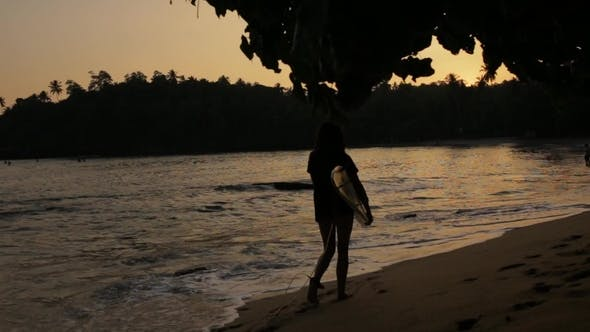 Girl with Surfboard Walking at Sunset