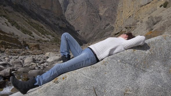 Thumbnail for Tourist Resting on a Rock Near a Mountain River Against a Background of Rocks