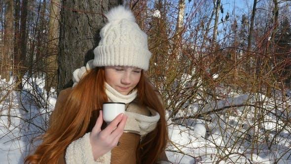 Rothaarige Mädchen Teenage Essen ein Brot und trinkt einen Tee am Winter Sunny Day