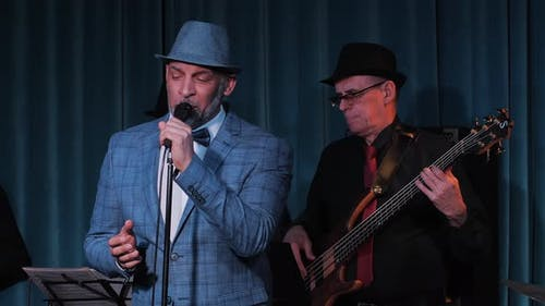 Jazz Singer and Guitarist in Black Suit and Hat Perform on Stage