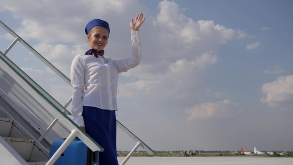 Cover Image for Female Airport Staff Waving Hand and Holds Suitcase on Stairs of Plane in Aeroport