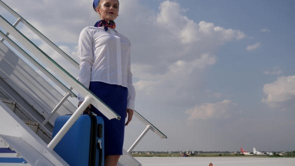 Thumbnail for Professional Stewardess Waving Hand and Holds Suitcase on Stairs of Plane in Aeroport