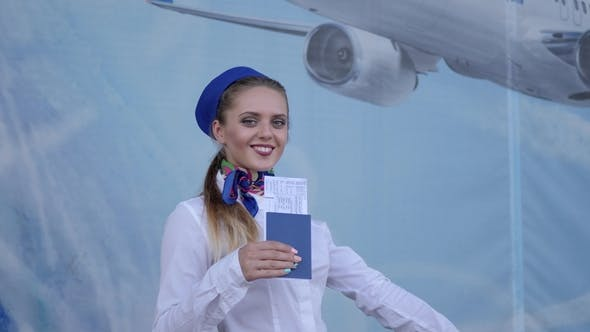 Cover Image for Happy Flight Attendant Holds in Hand Documents for Air Travel and Salutes at Camera